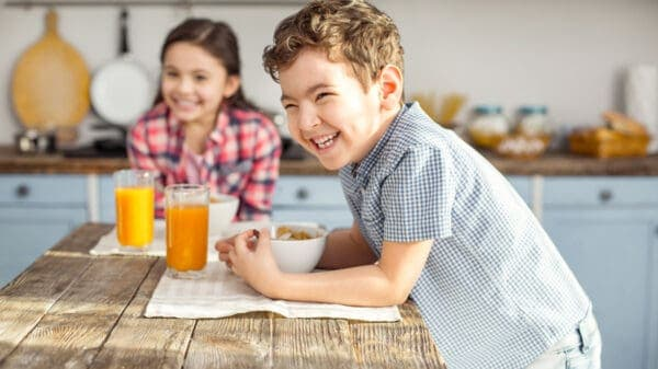Child eating cereal at table and smiling