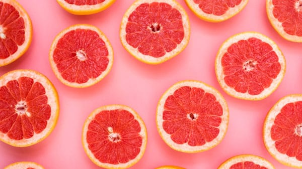 Grapefruit halves displayed on pink background