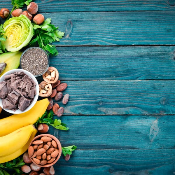 Nuts, legumes, fruits, and vegetables on blue background