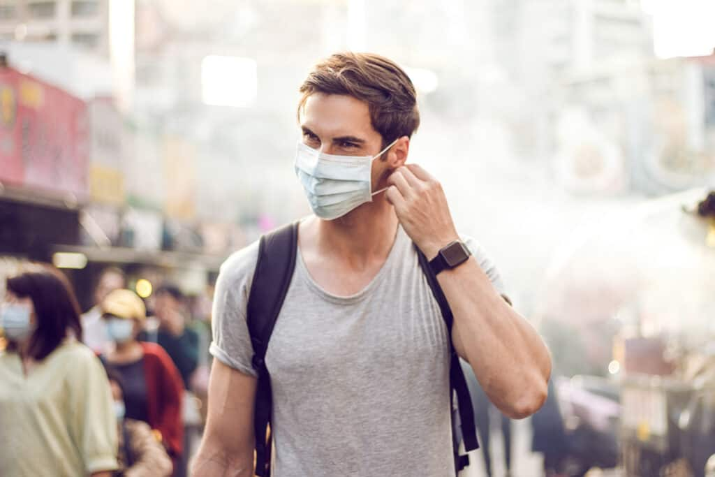 Man wearing face mask in a crowd
